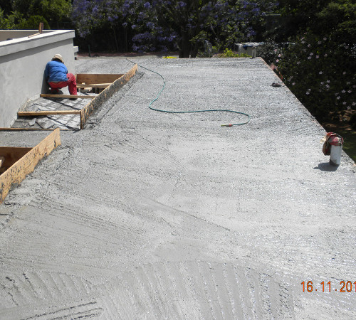 Concrete roof slab in, being floated and ready for screeding and waterproofing.